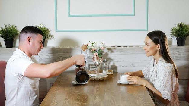 L'homme verse du thé savoureux dans une tasse de femme dans un café moderne et confortable