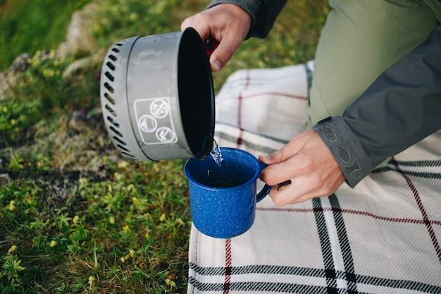 L'homme verse de l'eau de réchaud de camping à gaz