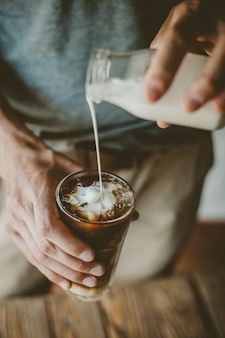 Homme, verser, lait, dans, café glacé