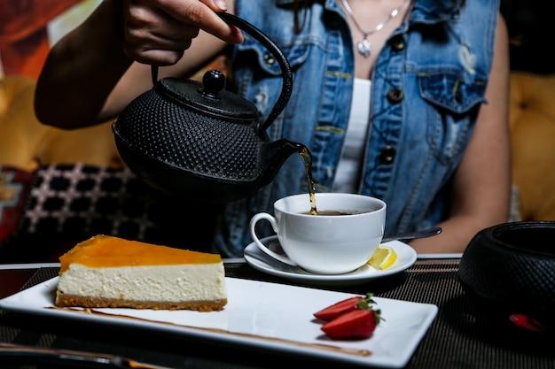 Homme, verser, thé, gâteau fromage, fraise, vue côté