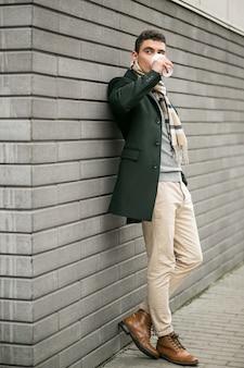 Homme en veste avec café