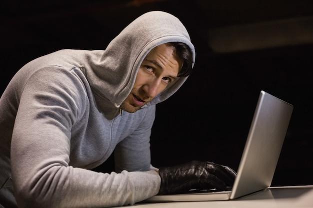 Homme en veste à capuche piratant un ordinateur portable tout en regardant la caméra