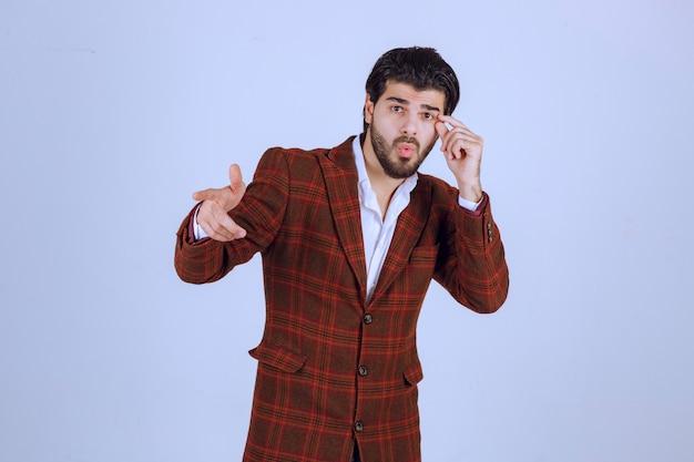 Homme en veste à carreaux marron pointant vers quelqu'un devant.
