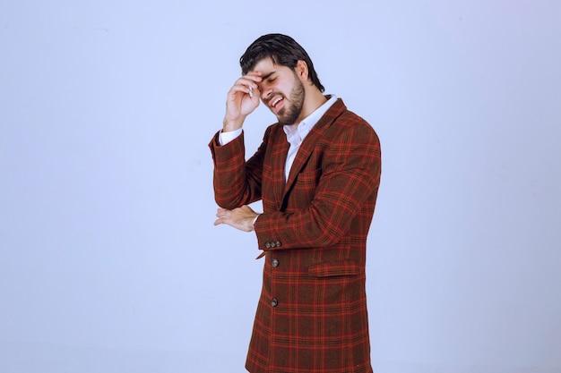 Homme en veste à carreaux mettant sa tête car il a mal à la tête ou se sent fatigué.