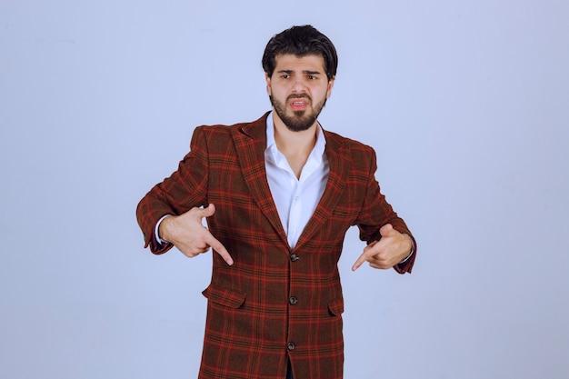 Homme en veste à carreaux pointant vers le bas avec le doigt et montrant quelque chose.