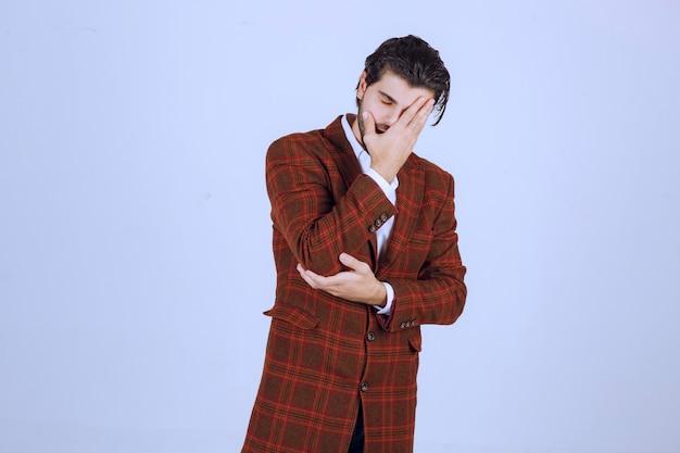 Homme en veste à carreaux se sentant très triste à propos de quelque chose et pleurant.