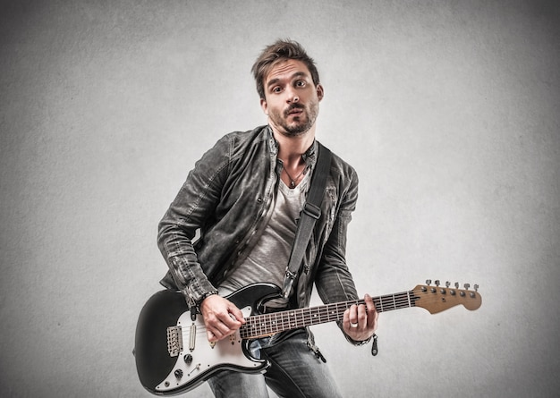 Homme en veste de cuir, jouant de la guitare