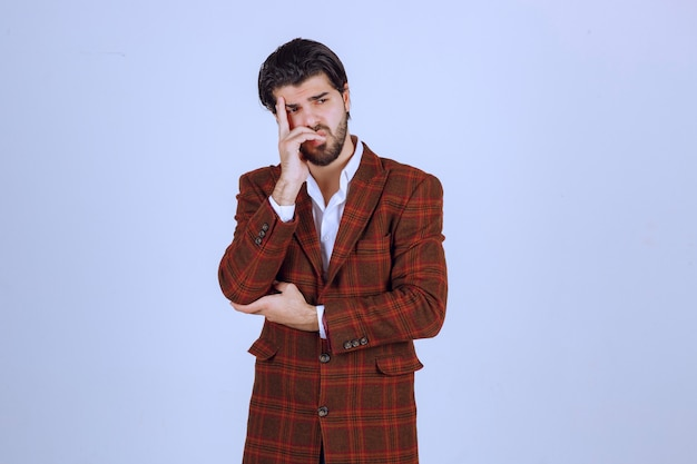 L'homme en veste marron a l'air pensif, confus et perdu.