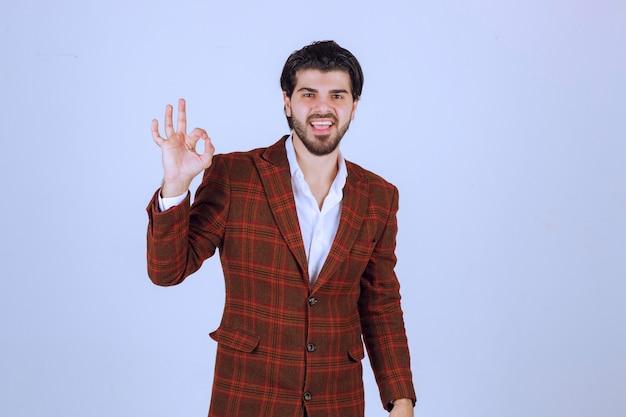 Homme en veste marron faisant signe de la main de la perfection.