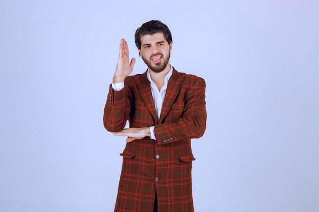 Homme en veste marron levant la main pour attirer l'attention.