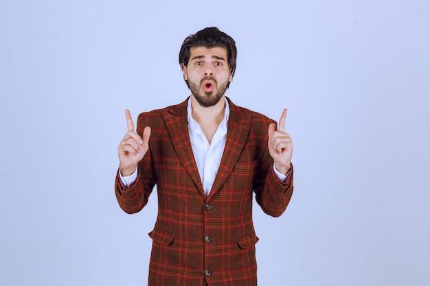 Homme en veste marron pointant vers le haut et présentant quelque chose.