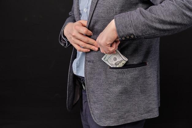 Un homme en veste met des dollars dans sa poche sur un espace noir.