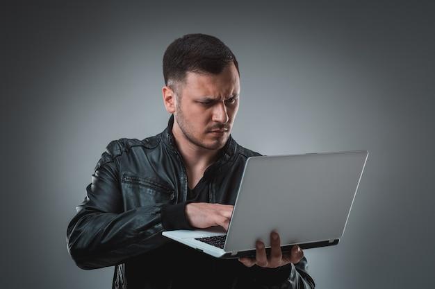 Homme en veste noire regardant un ordinateur portable, demi-tour. tenir un ordinateur portable ouvert et travailler. émotion.