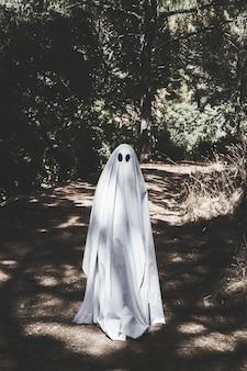 Homme en vêtements fantômes debout sur une passerelle dans le parc
