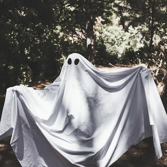 Homme en vêtements fantômes avec des mains en l'air dans la forêt