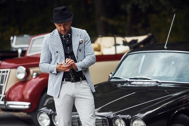 L'homme en vêtements formels et chapeau noir se tient près des automobiles rétro.