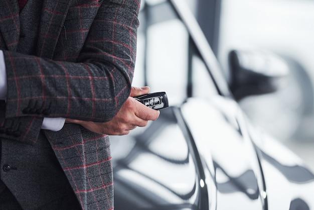 L'homme en vêtements formels modernes se dresse contre une voiture noire avec les clés en main.