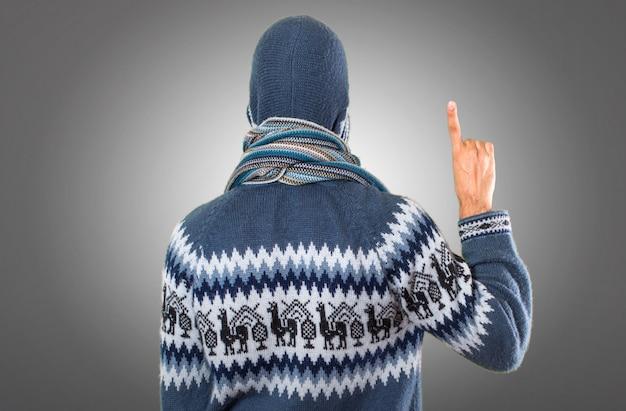 Homme avec des vêtements d'hiver comptant un sur fond gris