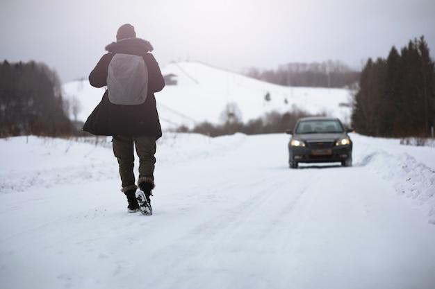 Un homme en vêtements d'hiver dans la rue. les touristes voyagent à travers le pays enneigé. sur le chemin, marchez et faites de l'auto-stop.