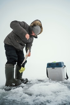 Homme en vêtements d'hiver pêchant seul à l'extérieur