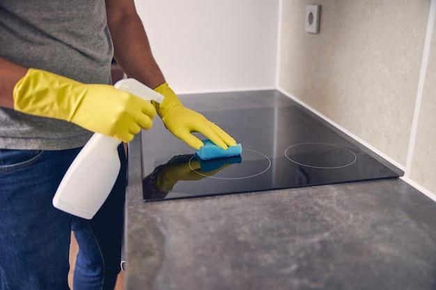 Homme en vêtements jaunes spéciaux utilisant un spray et du caoutchouc pour enlever la saleté d'un poêle