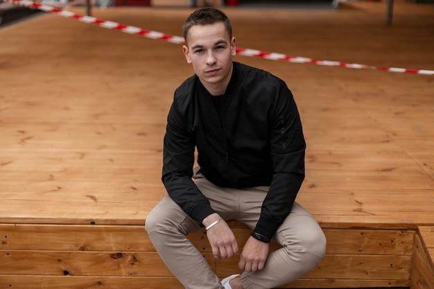L'homme en vêtements de mode est assis sur un plancher en bois à l'extérieur
