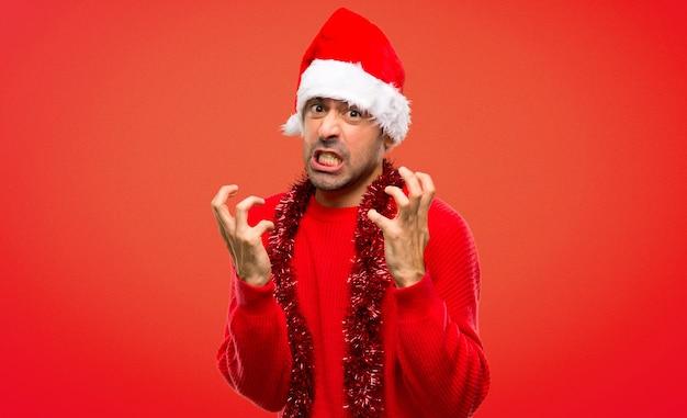 Homme avec des vêtements rouges célébrant les vacances de noël agacé colère en geste furieux