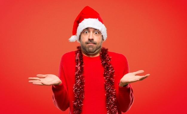 Homme avec des vêtements rouges célébrant les vacances de noël ayant des doutes en levant les mains
