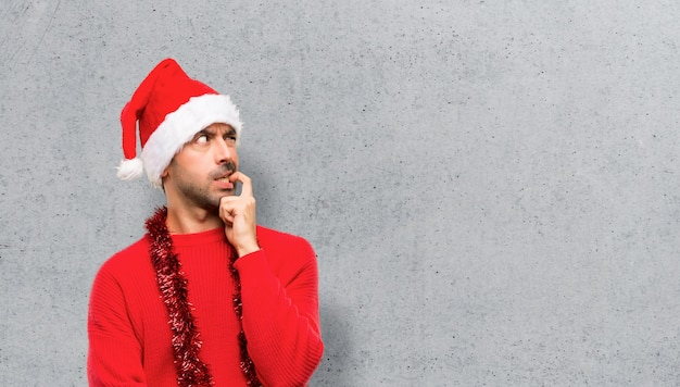 Homme avec des vêtements rouges célébrant les vacances de noël ayant des doutes tout en levant les yeux