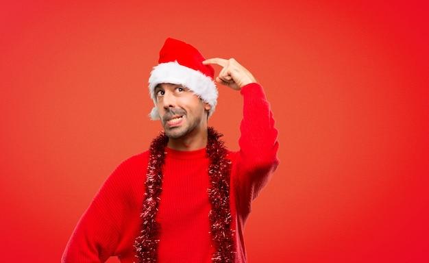 Homme avec des vêtements rouges célébrant les vacances de noël ayant des doutes