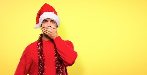 Homme avec des vêtements rouges, célébrant les vacances de noël, couvrant la bouche avec les mains