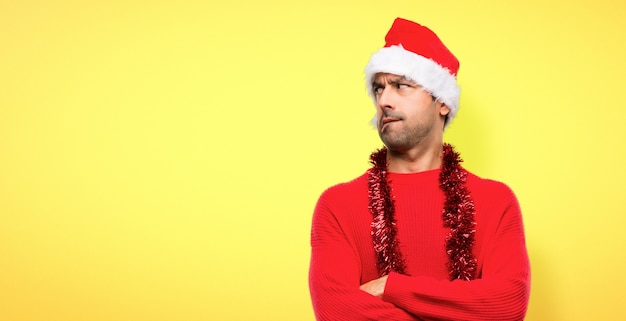 Homme avec des vêtements rouges célébrant les vacances de noël avec une expression du visage confuse