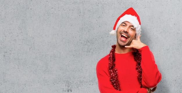 Homme avec des vêtements rouges, célébrant les vacances de noël, faisant un geste de téléphone.