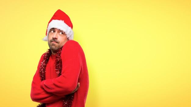 Homme avec des vêtements rouges, célébrant les vacances de noël, faisant des gestes de doutes