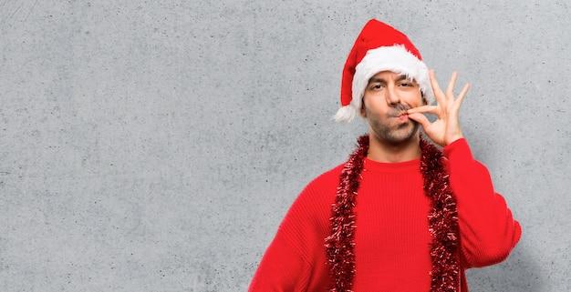 Homme avec des vêtements rouges, célébrant les vacances de noël, montrant un signe de fermeture de la bouche