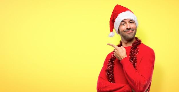 Homme avec des vêtements rouges célébrant les vacances de noël pointant vers le côté