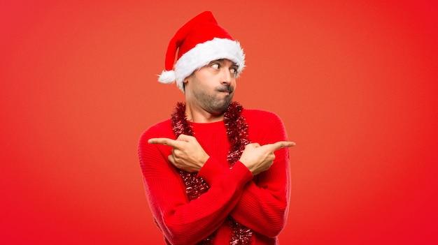 Homme avec des vêtements rouges célébrant les vacances de noël pointant vers les latéraux après avoir