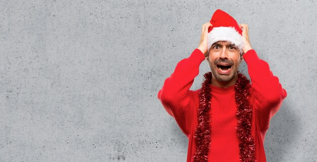 Homme avec des vêtements rouges célébrant les vacances de noël prend les mains sur la tête