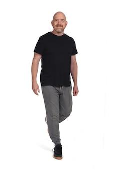 Homme avec des vêtements de sport marchant sur un fond blanc, avant