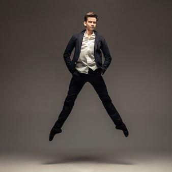 Homme en vêtements de style bureau décontracté sautant et dansant isolé sur fond gris