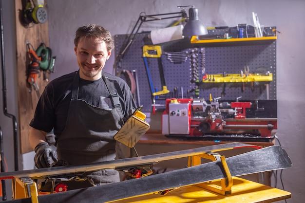 Un homme en vêtements de travail réparateur dans l'atelier de ski service de réparation du ski