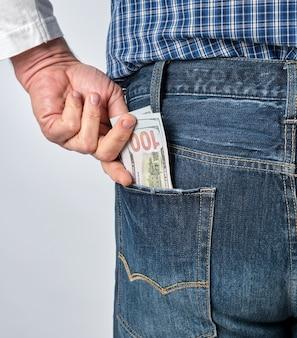 Un homme vêtu d'une chemise à carreaux bleue et d'un jean met des dollars américains en papier dans sa poche arrière