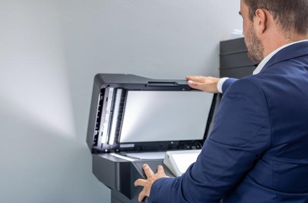 Homme vêtu d'un costume bleu prenant une photocopie au bureau.