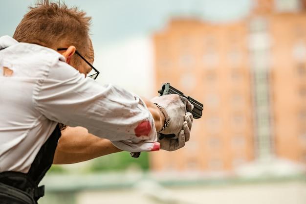 Un homme vêtu d'un gilet pare-balles, une chemise dans le sang, poursuit une victime avec une arme à feu