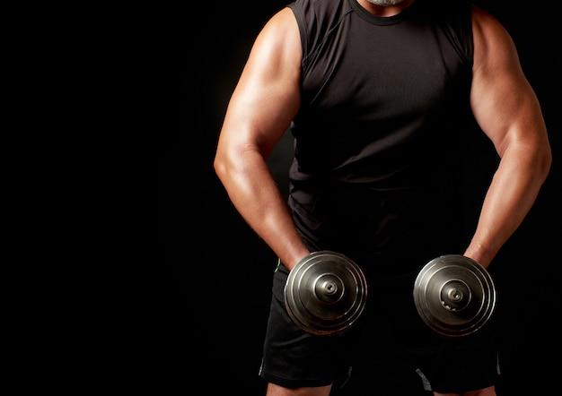 Un homme vêtu de noir tient des haltères en acier dans ses mains