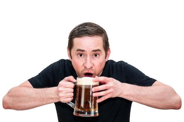 Un homme vêtu d'un t-shirt noir boit de la bière tout en tenant un verre à deux mains. fond blanc isolé.