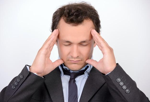 Homme vetu tenant la tête dans les mains et gardant les yeux.