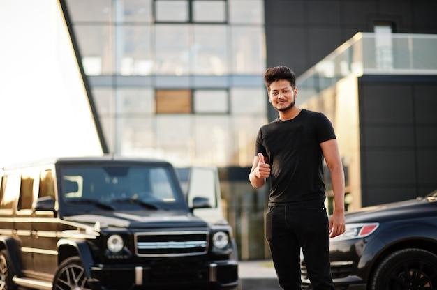 Homme vêtu de tout noir posant près de voitures suv