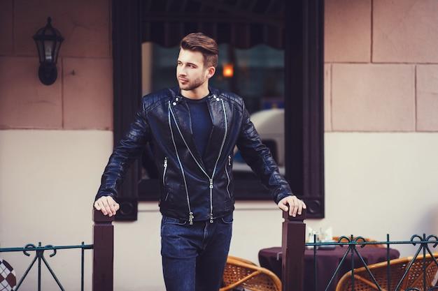 Un homme vêtu d'une veste en cuir posant dans la ville