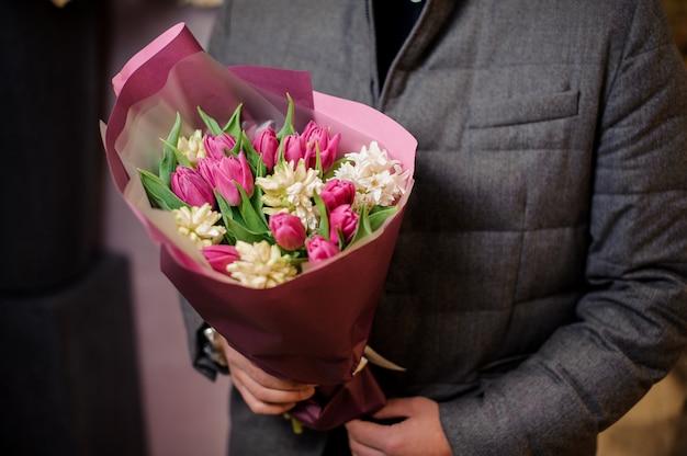 Homme vêtu d'une veste grise tenant un bouquet de fleurs